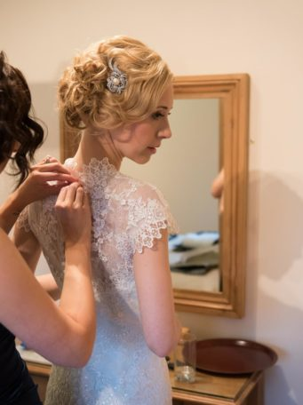 bride having the back of her dress done up
