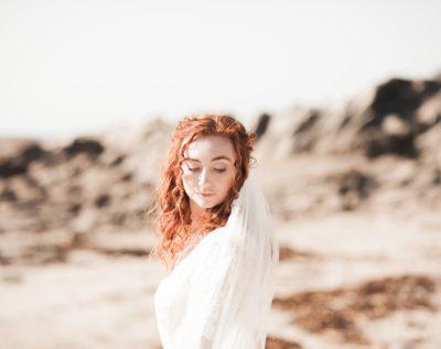 pretty bride looking down at the beach