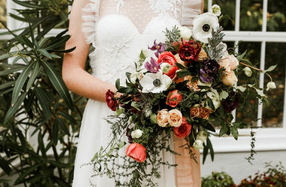 Bride holding wedding flowers at Burncoose House