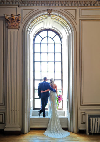 couple standing in front of window at Kimbolton Castle