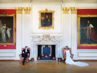 couple standing by the fireplace at Kimbolton Castle