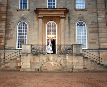 couple standing in front entrance at Kimbolton Castle