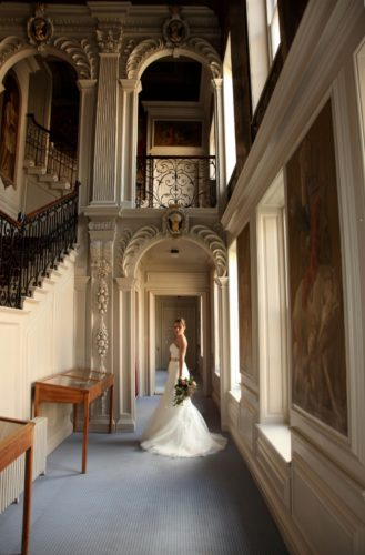bride by the window and sweeping stairs at Kimbolton Castle
