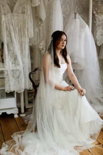 Bride wearing a custom wedding veil sitting in a bridal shop