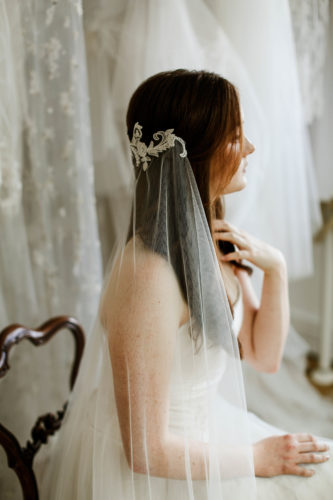 Bride wearing a custom hair accessory and wedding veil sitting in a bridal shop