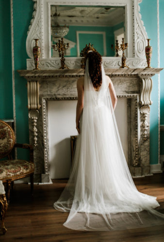 Bride wearing a custom veil standing in front of an ornate fireplace