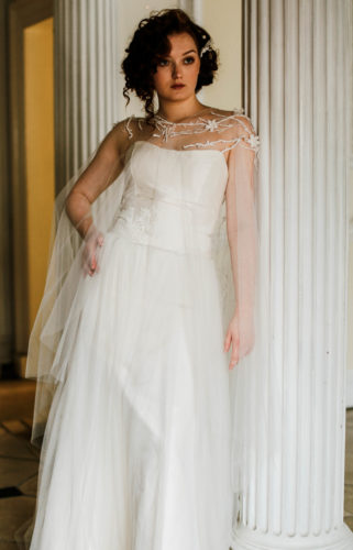 Bride wearing a custom cape standing by a pillar
