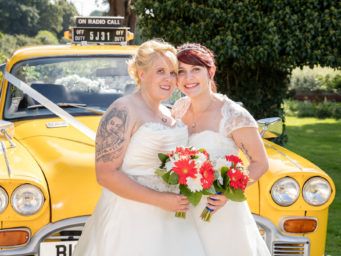 Two brides in front of their wedding car