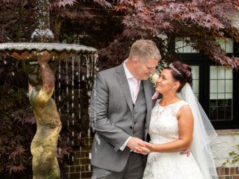 Bride and groom standing by the waterfall at Stanwick Courtyard Hotel