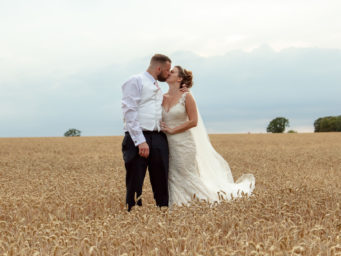 Bride and groom standing in a corn field