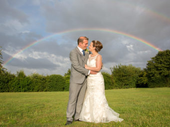 Bride and groom standing under a rainbow