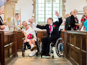 Disabled bride and groom at the alter of their wedding
