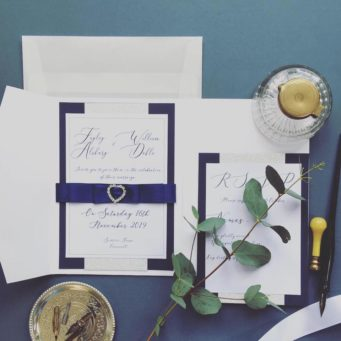 Classic navy wedding stationery with navy ribbon and diamanté heart