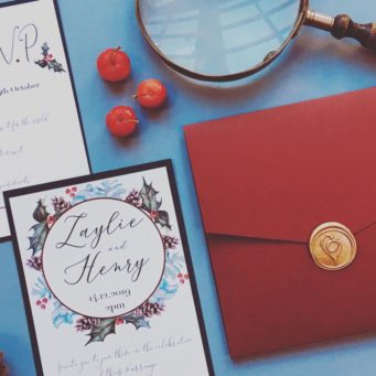 Christmas inspired wedding stationery with berries and red envelope sealed with gold wax