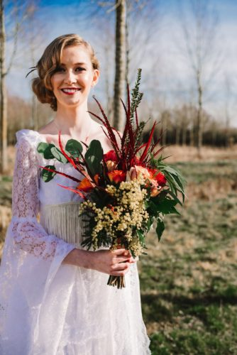 Bride standing with an elaborate bouquet by By Arrangement