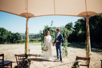 Bride and groom getting married outside under a floral arch with a tent in the foreground