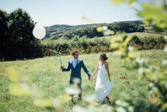 Bride and groom in the fields holding balloons at Camel Studio wedding venue