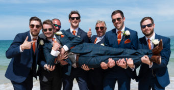 Groom being lifted by his best man and ushers