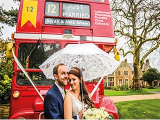 Newly married couple in front of red bus at Highgate House