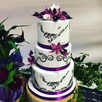 White wedding cake with purple ribbon and black lace