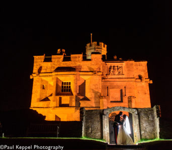 Bride and groom in front of the Castle Keep at night