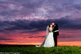 Bride and groom standing in the grounds of Pendennis Castle at sunset