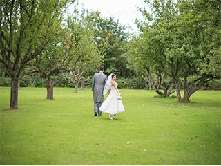 Newly wed couple walking on grass at their wedding venue