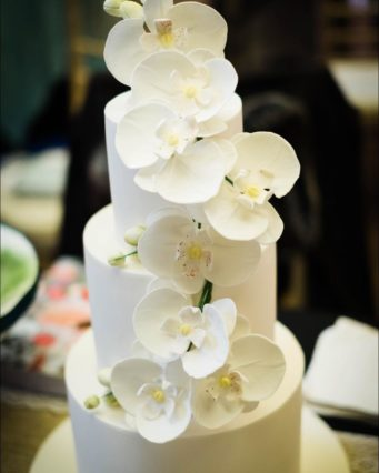 Simple white wedding cake with white orchids in sugar flowers