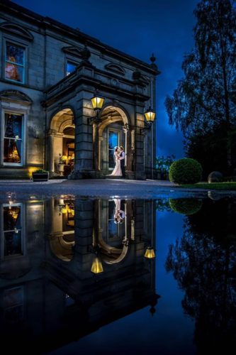 Couple at night at the front doors of Kilworth House Hotel with their reflection in the water