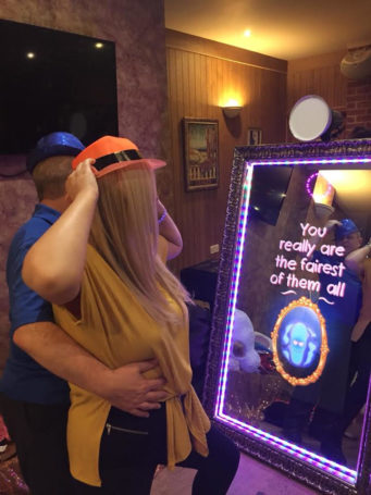 Couple having their photo taken by a mirror photo booth