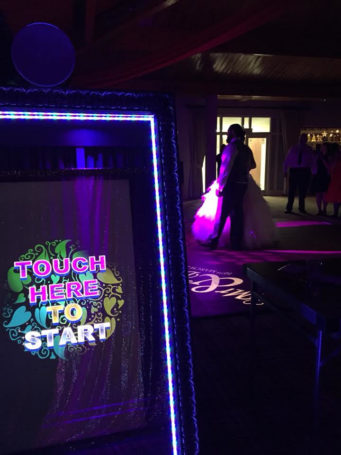 Mirror photo booth with a wedding couple dancing in the background