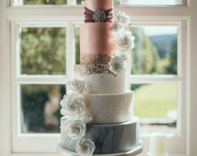 Stunning wedding cake of peach, gold, white and grey in front of window