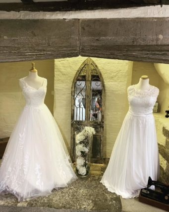 2 beautiful wedding dresses on a mannequin by a mirror