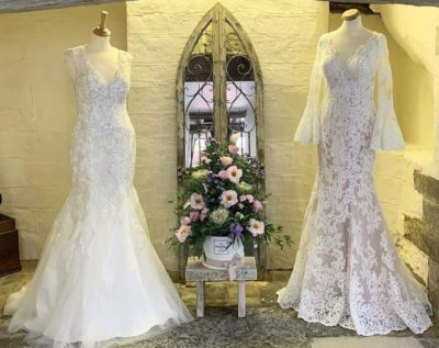 Stunning lace dresses standing in front of a mirror at Shop For Brides