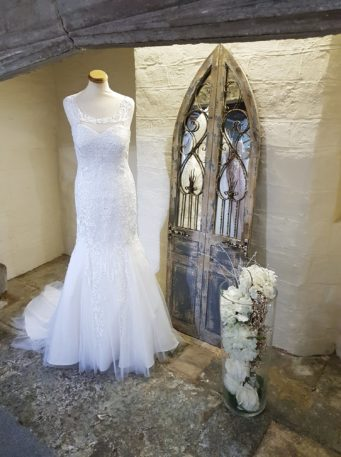 A lace wedding dresses on a mannequin by a mirror