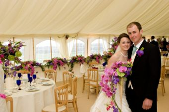 Bride and groom standing in their colourful marquee