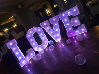 Giant love letters lit up with purple lights