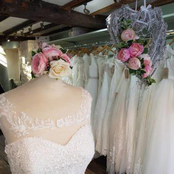 A close up of a wedding dress shown the top half