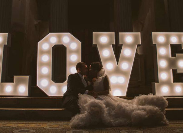 Couple sitting in front of giant love letters at Woburn Abbey