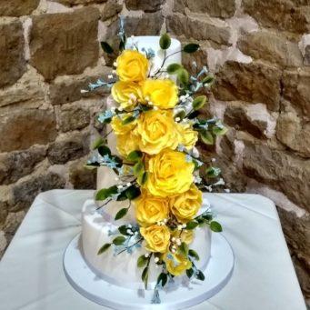 Beautiful wedding cake with yellow sugar roses tumbling down