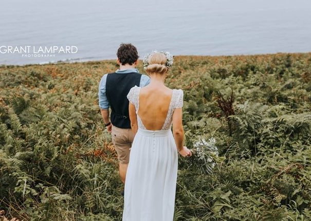 Bride and groom walking to their ceremony on a cliff top
