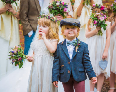 Little joyful children standing together outdoors at a wedding