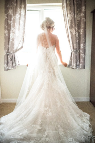 Bride standing by a window