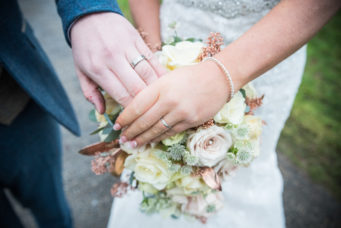 Bride and groom holding hands to show their rings