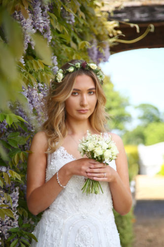 Bride holding a small bouquet and wearing a headdress