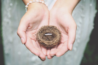 Bride holding her wedding band in a birds nest
