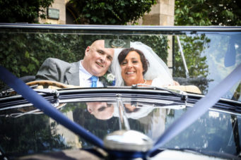 Bride and groom leaving in a vintage wedding car