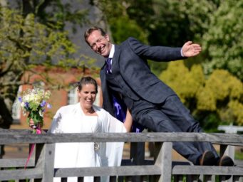 Bride and groom jumping around on a fence