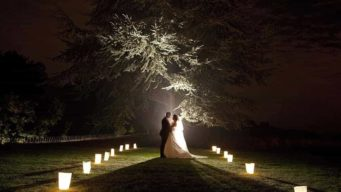 Bride & groom standing by a tree lit up at night