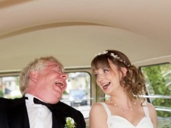 Bride laughing with her father in the car